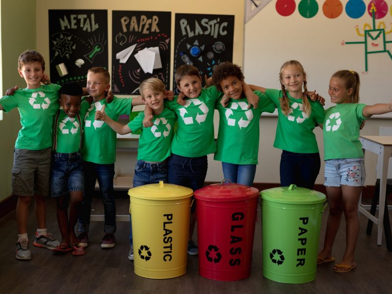 Portrait of a diverse group of schoolchildren wearing green t shirts with a white recycling logo on them, standing behind colour coded recycling bins in an elementary school classroom with arms around each other, smiling to camera with thumbs up